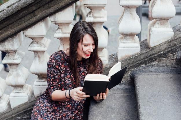 Menina, lendo um livro, rua