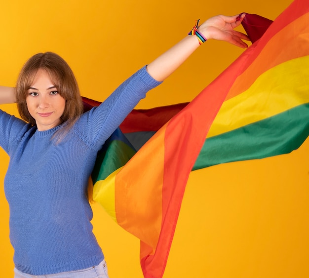 Menina lésbica bonita loira com bandeira do orgulho gay na parede amarela pastel