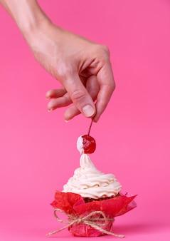 Menina leva cereja do bolo espalhado com creme. o conceito de prazeres sexuais. superfície rosa, tiro de estúdio