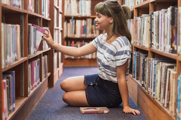 Menina, levando, livro, estante