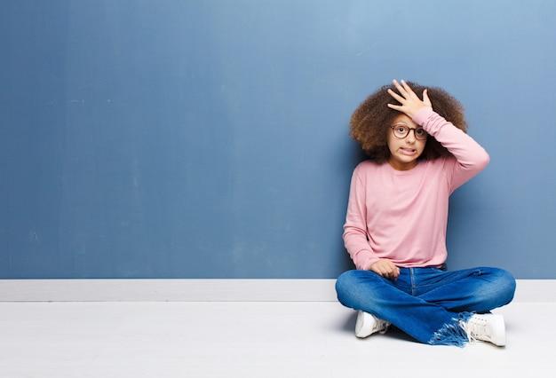 Menina, levantando a palma da mão para a testa, pensando, opa, depois de cometer um erro estúpido ou lembrar, sentindo-se idiota sentado no chão