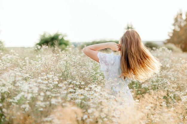 Menina levantando as mãos, bom dia, enquanto lindo pôr do sol