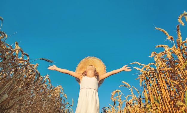 Menina levantando as mãos para o céu em um campo de trigo