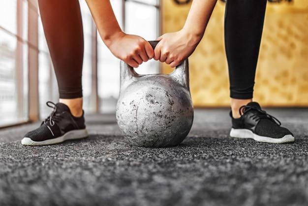 Menina levantando kettlebell do chão no ginásio