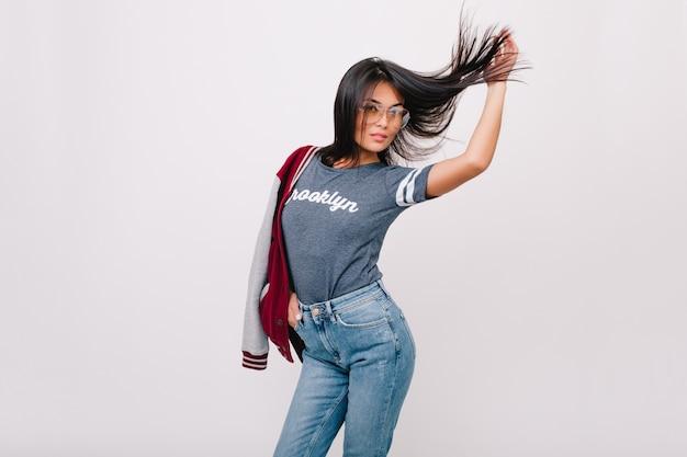Menina levemente bronzeada em jeans vintage, posando com cabelo preto balançando em frente a uma parede branca. adorável jovem de óculos se divertindo, dançando