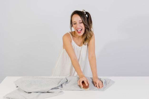 Menina limpa roupas com um pincel