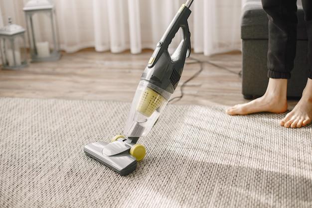 Menina limpando a casa com um aspirador de pó.