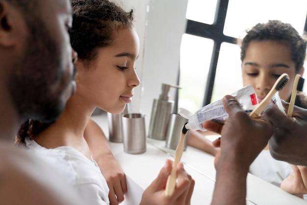 Menina limpando os dentes antes da escola ao lado do pai