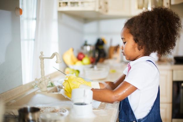 Menina limpando os pratos