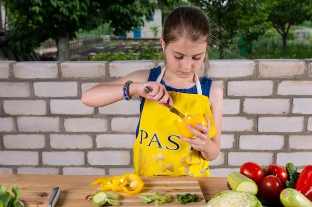 Menina limpando um pimentão e removendo a casca com uma faca enquanto prepara uma variedade de vegetais frescos