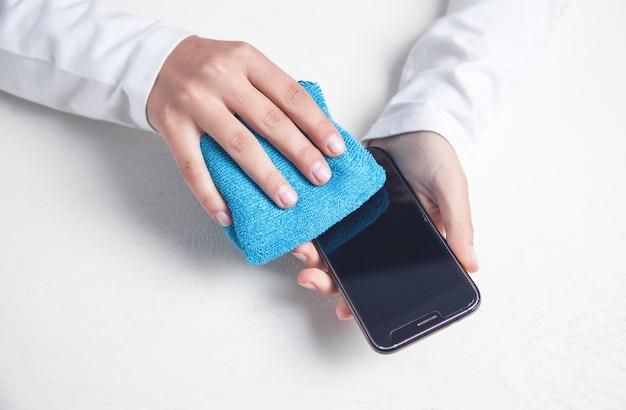 Menina limpeza smartphone no escritório.