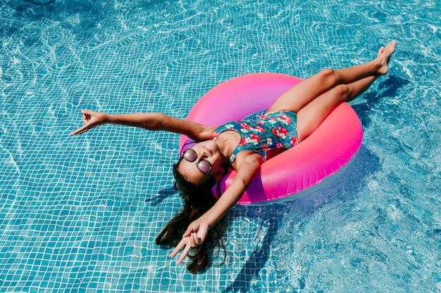 Menina linda adolescente flutuando em rosquinhas rosa em uma piscina. de óculos e sorrindo.