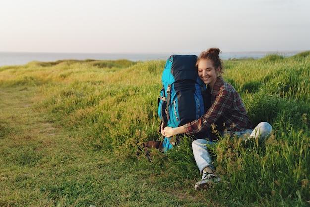 Menina linda alpinista abraçando sua mochila na grama e sorrindo