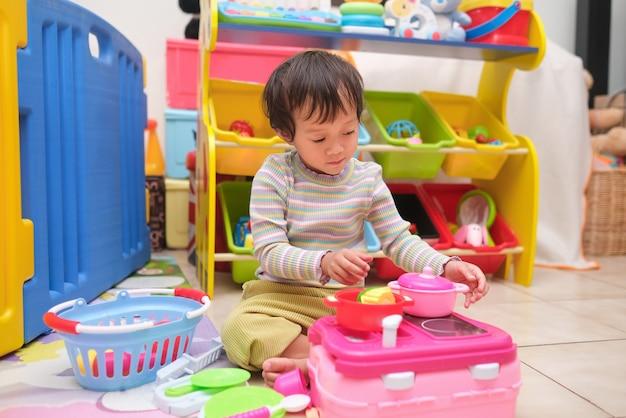 Menina linda asiática de 2 a 3 anos de idade se divertindo brincando sozinha com brinquedos de cozinha