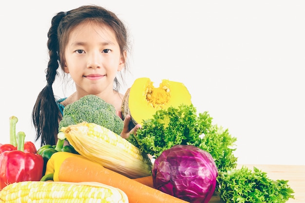 Menina linda asiática mostrando desfrutar de expressão com legumes coloridos frescos