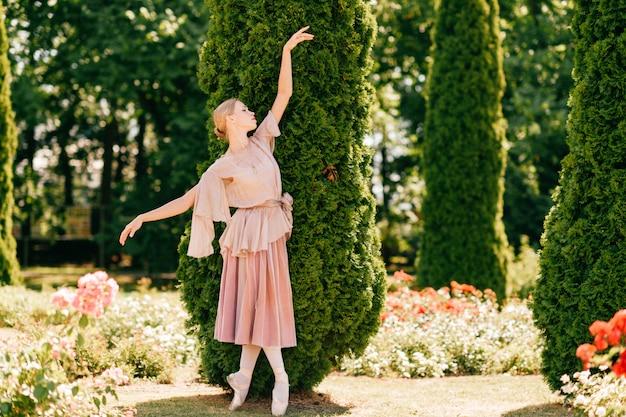 Menina linda bailarina posando com emoção dramática no parque de verão.