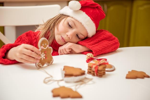 Menina linda brincando com biscoitos de gengibre