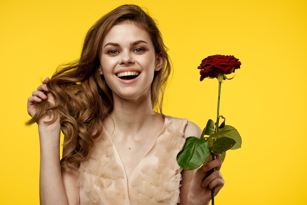 Menina linda com aparência angelical com uma flor rosa nas mãos