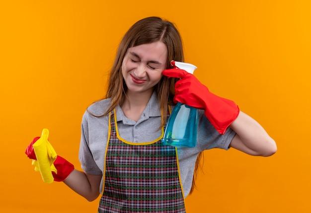 Menina linda com avental e luvas de borracha segurando um spray de limpeza perto da têmpora como uma arma com uma expressão irritada