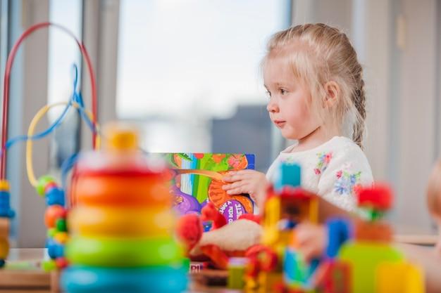 Menina linda com brinquedos no jardim de infância