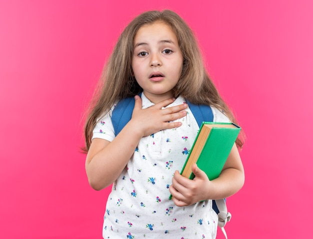 Menina linda com cabelo comprido com mochila segurando o caderno espantada e surpresa segurando a mão no peito em pé na rosa