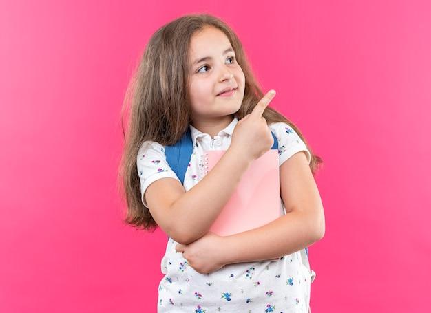 Menina linda com cabelo comprido com mochila segurando o caderno olhando para cima com um sorriso no rosto apontando com o dedo indicador para o lado em pé sobre a parede rosa