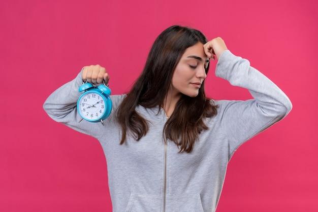 Menina linda com capuz cinza olhando para longe com a mão na testa pensando, segurando o relógio em pé sobre fundo rosa