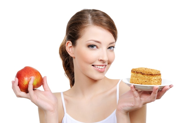 Menina linda com frutas e bolo nas mãos
