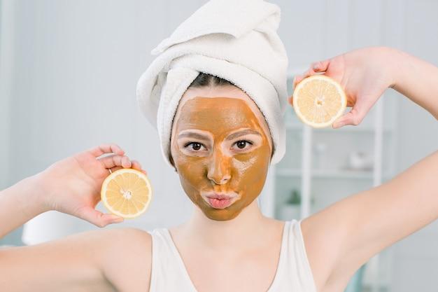 Menina linda com máscara facial marrom, segurando uma fatia de limão perto do rosto e sorrindo. foto de menina recebendo tratamentos de spa. conceito de beleza e cuidados com a pele