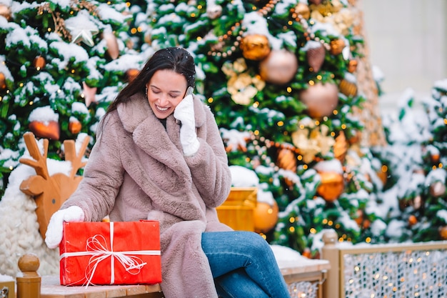 Menina linda com presente vermelho no natal com smartphone na neve ao ar livre