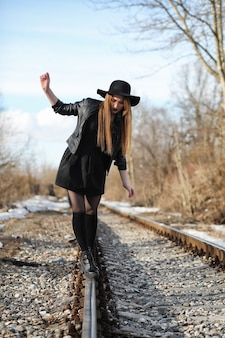 Menina linda com um chapéu e uma maquiagem escura do lado de fora. garota em estilo gótico na rua. uma garota caminha pela rua da cidade em um colete de couro com telefone.