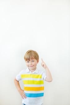 Menina linda criança aponta o dedo para cima. copie o espaço