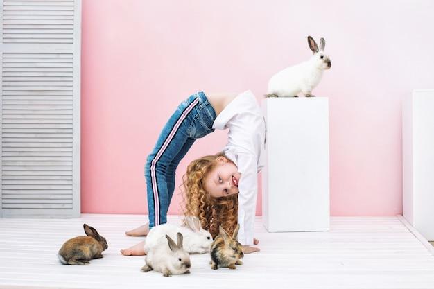 Menina linda criança com cabelo encaracolado e coelhos de animais fofos em fundo rosa
