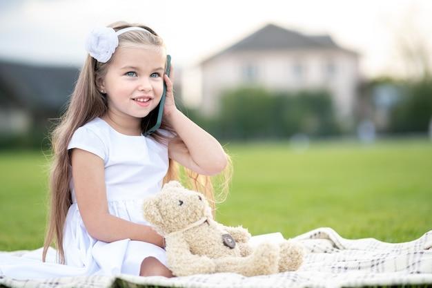 Menina linda criança descansando no parque de verão na grama verde com seu ursinho de pelúcia brinquedo falando no celular ao ar livre no verão.