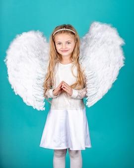 Menina linda criança em um vestido branco de pé sobre um anjo de criança de fundo de cor com um lindo feltro de asas.