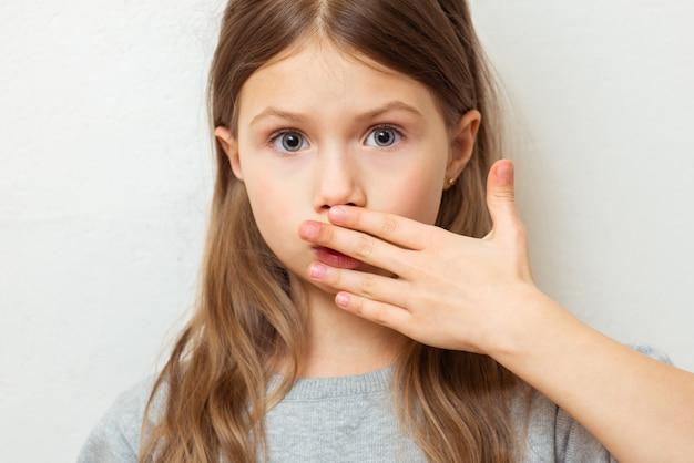Menina linda criança fecha a boca com a mão tímida de qualquer coisa. período menstrual pela primeira vez, conceito