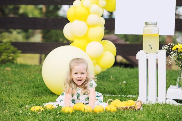 Menina linda criança linda e feliz na grama verde com balões e limonada