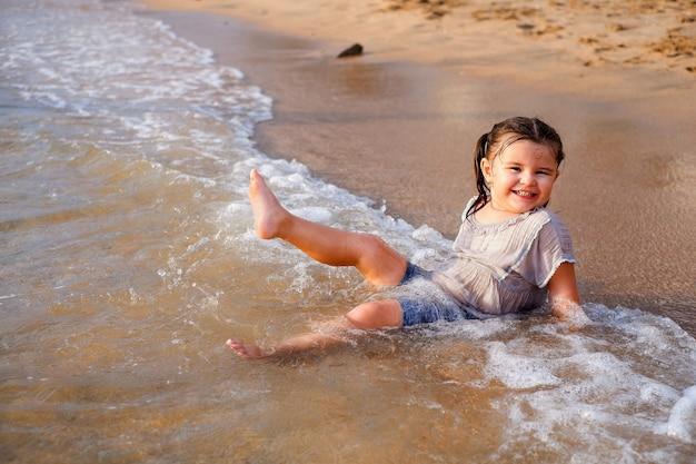 Menina linda criança se divertindo na praia. senta na água com ondas e ri