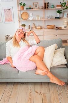Menina linda curtindo a manhã no sofá com cobertor rosa