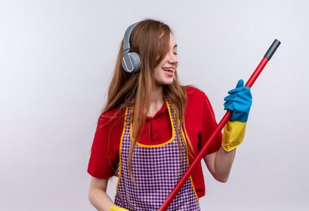 Menina linda de avental e luvas de borracha com fones de ouvido na cabeça segurando o esfregão curtindo sua música favorita