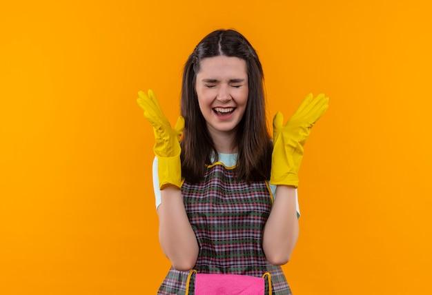 Menina linda de avental e luvas de borracha feliz e animada levantando os braços