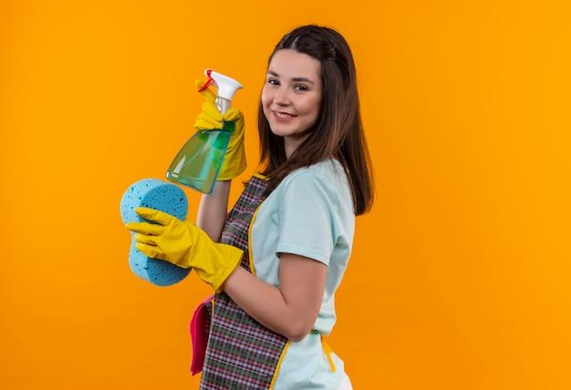 Menina linda de avental e luvas de borracha segurando spray de limpeza e esponja olhando para a câmera sorrindo com uma cara feliz de pé de lado sobre um fundo laranja