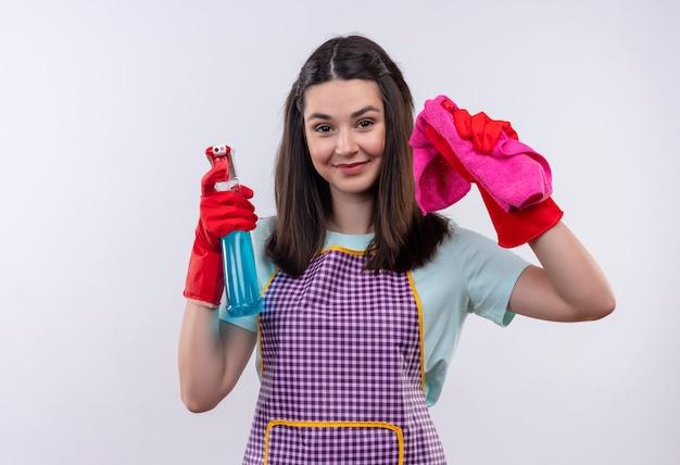 Menina linda de avental e luvas de borracha segurando spray de limpeza e tapete, olhando para a câmera, sorrindo alegremente, pronta para limpar