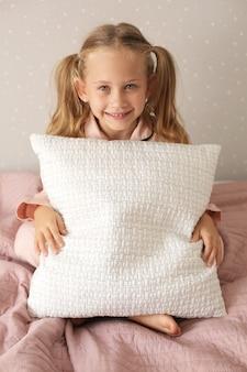 Menina linda de pijama rosa sentada em um cobertor rosa na cama em casa abraçando um travesseiro