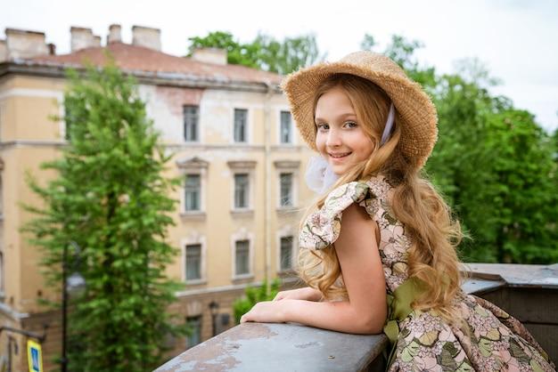 Menina linda de vestido e chapéu posando na varanda contra a cena da cidade