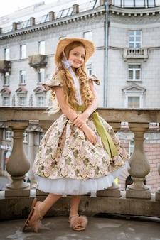 Menina linda de vestido e chapéu posando na varanda na cidade