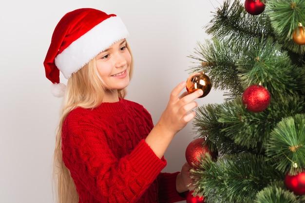 Menina linda decorando a árvore de natal