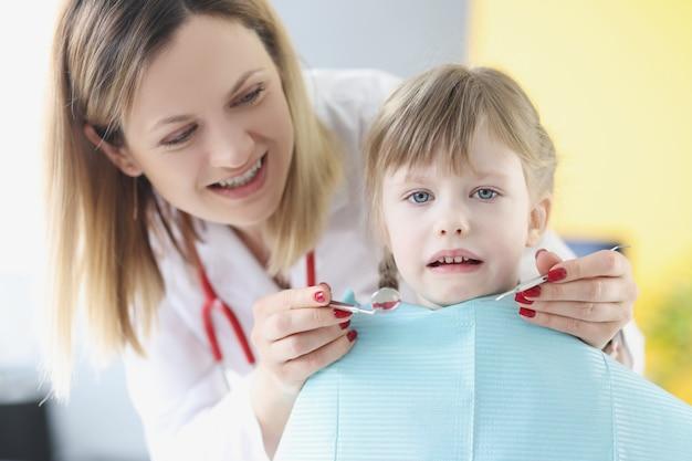 Menina linda e assustada sentada na cadeira no exame dentário e no tratamento dos dentes decíduos