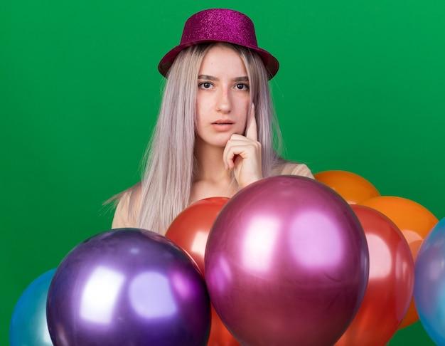 Menina linda e desagradável com chapéu de festa em pé atrás de balões, colocando o dedo na bochecha