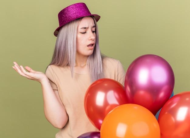 Menina linda e desagradável com chapéu de festa em pé atrás de balões, espalhando a mão isolada na parede verde oliva